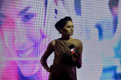 An Indian model showcases the new Samsung 'Galaxy S5' smartphone during a fashion show held as part of a consumer event in Banga
