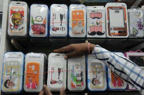 An Indian shopkeeper arranges freshly arrived snap-on mobile phone covers at his shop in Mumbai on April 2, 2014