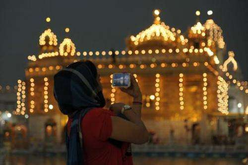 An Indian Sikh devotee takes a photograph on her mobile phone in the front of the illuminated Sikhism's holiest shrine, the Gold
