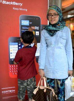 An Indonesian woman and her son stand next to a Blackberry advertisement board at a shopping mall in Jakarta, May 10, 2014