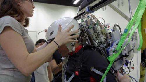 A paraplegic patient (R) wears an interface helmet at Brazilian scientist Miguel Nicolelis' lab in Sao Paulo, Brazil, on January