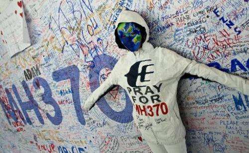 A performer poses in front of messages expressing prayers and well-wishes for passengers onboard missing Malaysia Airlines fligh