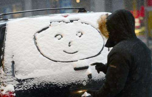 "A person draws a ""happy face"" on a car window during a snow storm in New York, January 21, 2014"