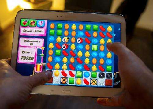 A person plays on his tablet Candy Crush Saga game, developed by King Digital Entertainment, in Lille, northern France, on March