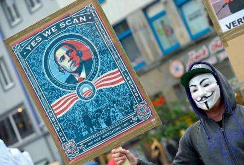A protestor wearing a Guy-Fawkes-mask holds a banner with a picture of US President Barack Obama to protest against the NSA inte