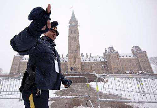 A Royal Canadian Mounted Police (RCMP) officer checks a security perimeter in front of the Parliament building in Ottawa, Ontari