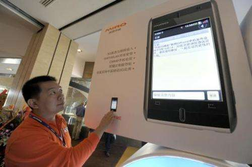 A staff member checks a Lenovo mobile phone display prior to a launching ceremony in Beijing, on September 16, 2009