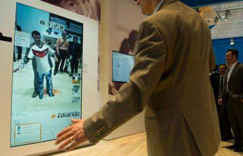 A visitor tries on clothes in a virtual fitting room at the stand of South Korean electronics giant Samsung at the 2014 CeBIT co