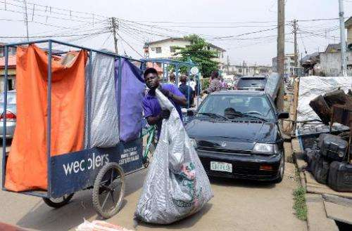 A 'Wecycler' worker collects recyclable goods from customers in Surulere district of Lagos, on January 17, 2014