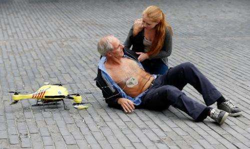 A woman gives a demonstration of an ambulance drone with a built in defibrillator at the campus of the Delft Technical Universit