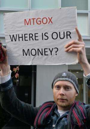 Bitcoin trader Kolin Burges from Britain holds up a placard to protest against Tokyo-based bitcoin changer MtGox in front of the
