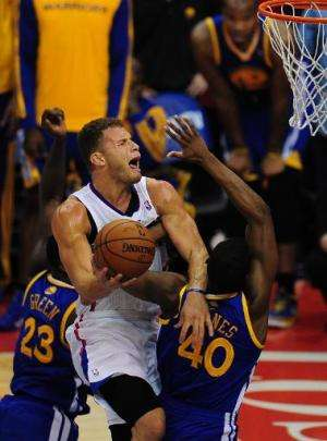 Blake Griffin of the Los Angeles Clippers draws a foul while driving to the hoop to score under pressure from Jermaine O'Neal (#