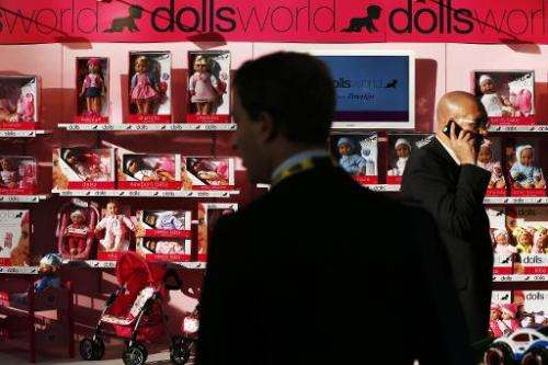 Businessmen look at the Doll World stand during the annual Toy Fair at the Olympia exhibition centre in London, on January 21, 2