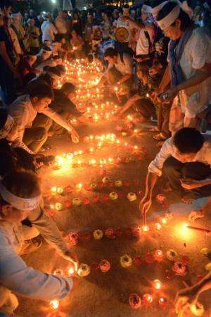Cambodians light candles as they pray for the missing Malaysia Airlines flight MH370 in Phnom Penh on March 17, 2014