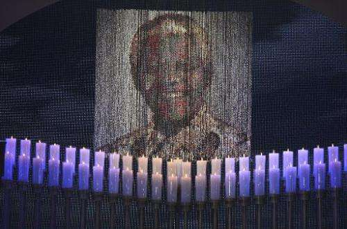 Candles are lit under a portrait of Neslon Mandela before the funeral of the former South African president in Qunu on December