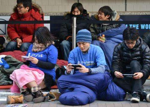 Customers queue outside the Sony building in Tokyo's Ginza shopping district on February 21, 2014 to get numbered tickets to pur