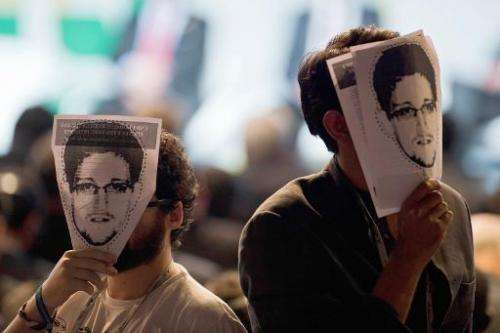 "Demonstrators hold portraits of Edward Snowden at a protest during the opening ceremony of the ""NETmundial – Global Multist"