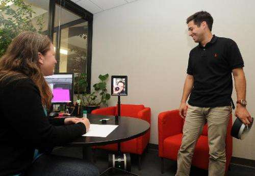 Employees speak with David Cann (C), CEO and Co-founder of Double Robotics, on a Telepresence 'Double' Robot, at the company's h