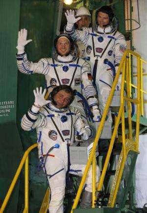 European Space Agency's German astronaut Alexander Gerst (C), Russian cosmonaut Maxim Suraev (bottom) and US NASA astronaut Greg