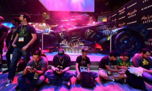 "Gaming fans take a break beside the Batman ""Arkham Knight"" display at the annual E3 video game extravaganza in Los Ang"