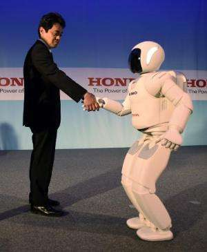 Honda's Satoshi Shigemi works with Asimo Robot at a news conference demonstration on April 16, 2014 in New York