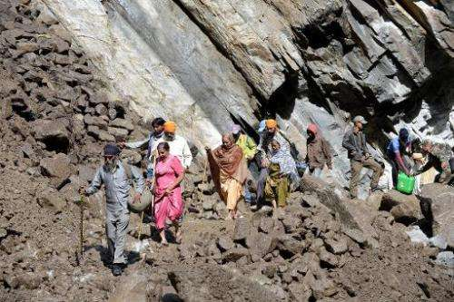 Indian Hindu pilgrims and villagers make their way across a landslide as they walk through Govindghat following flash floods in