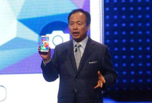 JK Shin, head of Samsung Mobile Communications, presents a Galaxy S5 smartphone during a press conference at the Mobile World Co