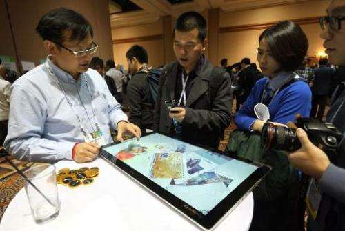 Journalists watch a presentation of Lenovo's new Horizon 2 table PC, a 27-inch, 10-point touchscreen that can be paired to an An