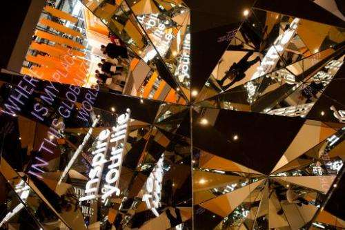 Kaleidoscopic mirrors reflect slogans and fair visitors at the stand of German software giant SAP at the 2014 CeBIT computer tec