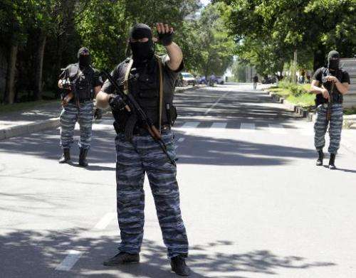 Masked armed men wearing uniforms with the emblem of the Berkut, Ukraine's bisbanded elite riot police force, block the road in