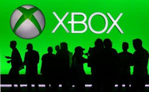 People are silhouetted against an Xbox display at annual E3 video game extravaganza in Los Angeles, California on June 10, 2014