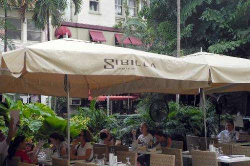 People eat at the terrace of an Italian restaurant in Miami Beach, Florida on October 11, 2011