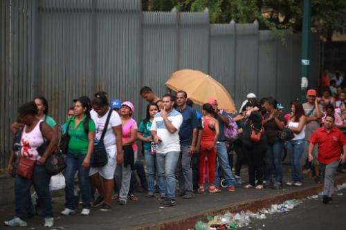 People queue up outside a supermarket to buy food in Caracas April 2, 2014