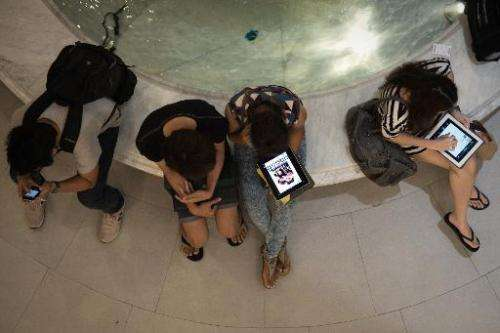 People use their smartphones and tablets in a shopping mall in Bangkok on March 19, 2013
