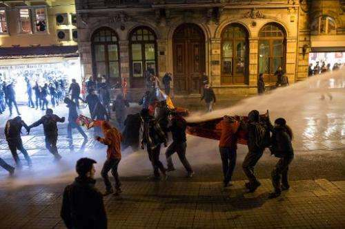 Police use a water cannon to try to disperse people protesting against newly proposed restrictions on the use of the internet an