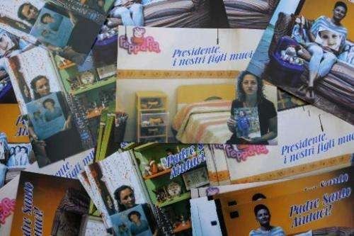 Postcards displayed in Caivano, southern Italy, on November 14, 2013 show mothers with pictures of their children who died from