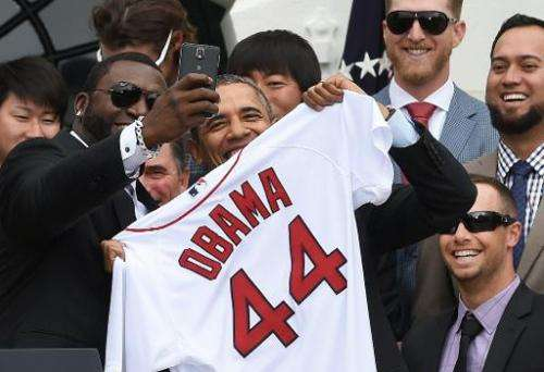 "Red Sox Designated Hitter David Ortiz (L) takes a ""selfie"" with US President Barack Obama during a ceremony on the Sou"
