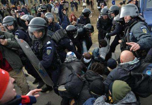 Romanian protesters scuffle with gendarmes after breaking the fence at Chevron's exploratory well in Pungesti, Romania on Decemb