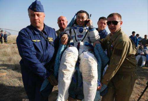 Russian space agency rescue team members carry Japanese astronaut Koichi Wakata shortly after landing, about 150 km south-east o