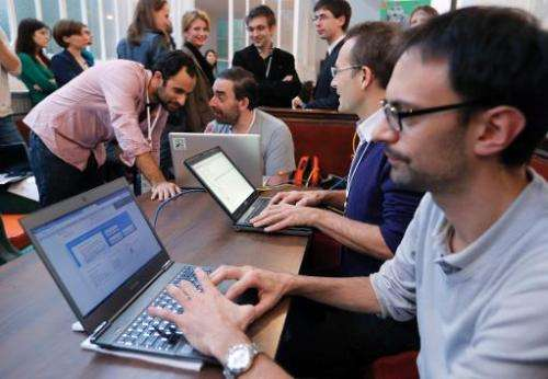 Software developers work during the hack event 'Hackathon Dataculture' in Paris on October 25, 2013