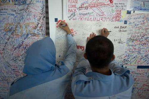 Students write on a placard carrying messages for the passengers of missing Malaysia Airlines flight MH370 at Kuala Lumpur Inter