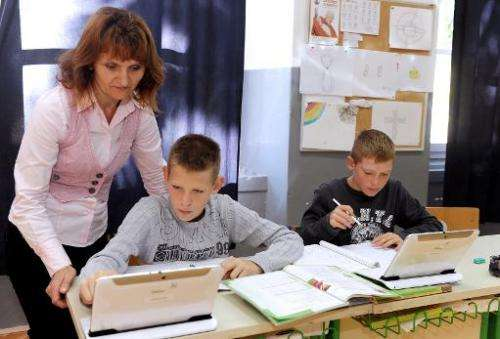 Teacher Barbara Busic-Ribaric (C) helps pupils Dominik Malovic (L) and Ivan Macic (R) at their school on the small remote island