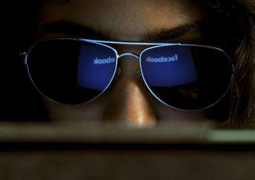 The 'Facebook' logo is reflected in a young Indian woman's sunglasses as she browses on a tablet in Bangalore on May 15, 2012