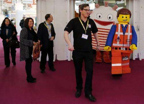 Toy characters walk past visitors during the Toy Fair at Olympia exhibition centre  in London on January 21, 2014