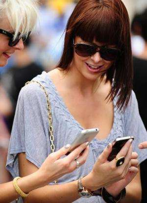 Two women look at smartphones in front of Manhattan's 5th Avenue Apple store on June 24, 2010 in New York