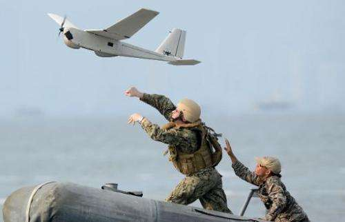 US and Philippine navy personnel launch an unmanned aerial vehicle from a speed boat off the naval base in Sangley point, Cavite