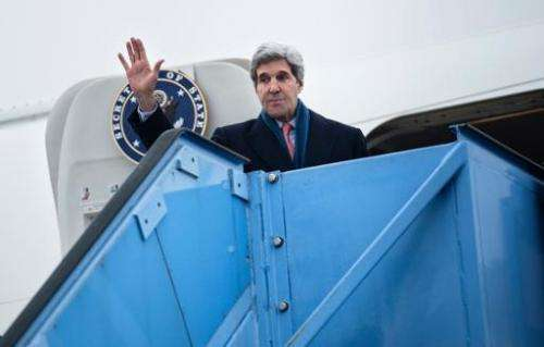 US Secretary of State John Kerry waves while boarding his plane at Franz-Josef-Strauss Airport in Munich, southern Germany, on F
