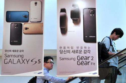 Visitors pass signboards for Samsung Electronics' Galaxy S5 at its showroom in Seoul on April 29, 2014