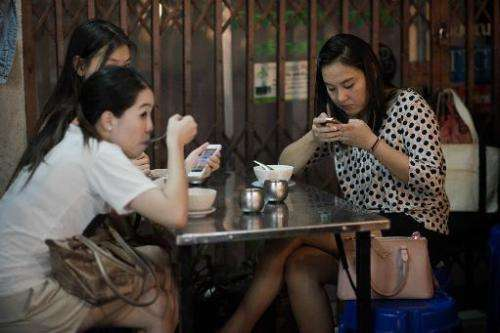 Women look at their smartphones while having dinner at a street food restaurant in Bangkok on March 19, 2013
