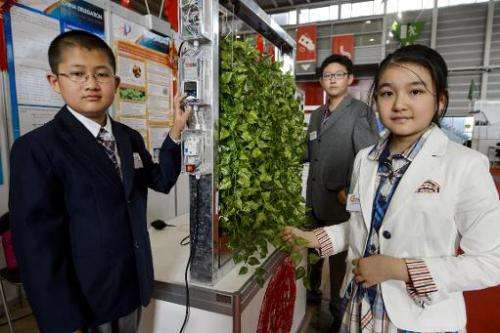 Young inventors from Beijing, China, (from L) Fan Xiyu, Li Peize and Wang Yifan present their creation during the opening day of